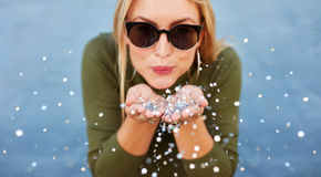 Attractive young woman blowing glitters Stock Photography