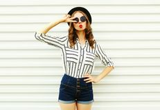Attractive young woman blowing red lips sending sweet air kiss in black round hat, shorts, white striped shirt on white wall. Background stock image