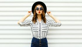 Attractive young woman blowing red lips sending sweet air kiss in black round hat, shorts, white striped shirt on white wall. Background stock images