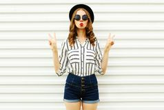 Attractive young woman blowing red lips sending sweet air kiss in black round hat, shorts, white striped shirt on white wall royalty free stock images