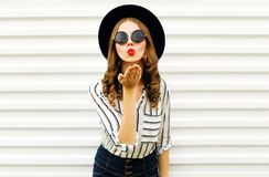 Attractive young woman blowing red lips sending sweet air kiss in black round hat, shorts, white striped shirt on white wall. Background royalty free stock image