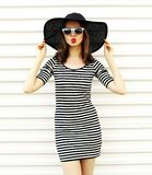 Attractive young woman blowing red lips sending sweet air kiss in black summer straw hat on white wall. Background royalty free stock images