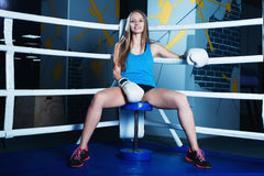 Attractive young woman with blue boxing gloves. Sitting in the corner of boxing ring Stock Images