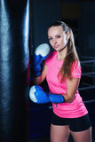 Attractive young woman with blue boxing gloves in sport gym. Beautiful female boxer with punching bag. Stock Photo