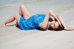 Attractive young woman in blue dress on the beach Stock Photo