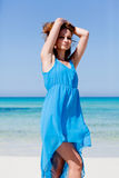 Attractive young woman in blue dress on the beach. Sandy holiday Stock Photo