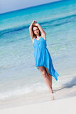 Attractive young woman in blue dress on the beach Royalty Free Stock Photo