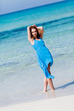 Attractive young woman in blue dress on the beach. Sandy holiday Stock Photography