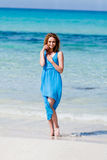Attractive young woman in blue dress on the beach. Sandy holiday Royalty Free Stock Photo