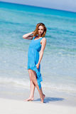 Attractive young woman in blue dress on the beach. Sandy holiday Stock Photos