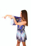 Attractive young woman in a blue dress points to the left Royalty Free Stock Photos