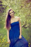 Attractive young woman in blue long dress outdoor portrait Royalty Free Stock Image