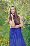 Attractive young woman in blue long dress outdoor portrait Stock Photo