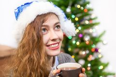 Attractive young woman in blue Santa hat holding hot tea mug in hands Stock Photo