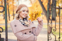 Attractive young woman with a bouquet of leaves. Royalty Free Stock Images