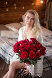 Attractive young woman with bouquet of red roses in the morning. Stock Images