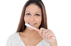 Attractive young woman with brackets cleaning her teeth Royalty Free Stock Photography