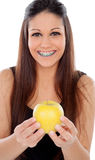 Attractive young woman with brackets eating a apple Stock Photos