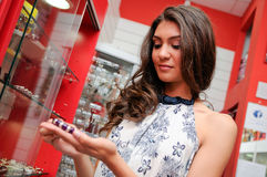 Attractive young woman buying a bracelet at a jewelry Royalty Free Stock Images