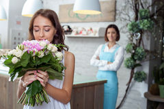 Attractive young woman is buying flowers in store Royalty Free Stock Photo