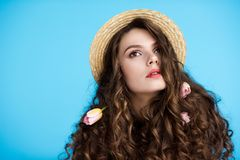 attractive young woman in canotier hat with flowers in her long curly hair stock images