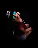 Attractive young woman in cap and sunglasses, smokes on a dark background. Be trendy, be rapper Stock Photography