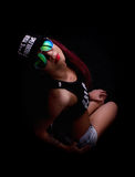 Attractive young woman in cap and sunglasses, smokes on a dark background. Be trendy, be rapper Royalty Free Stock Image