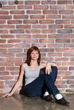 Attractive young woman in casual clothes, blue jeans and vest grey is looking at camera and smiling sitting on a floor royalty free stock photography