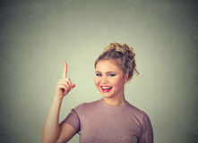 Attractive young woman in casual clothes pointing her finger up has an idea stock photography