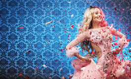 Attractive young woman celebrating among rose petals Royalty Free Stock Photography