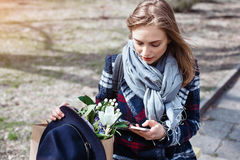 Attractive young woman chatting on cell telephone on a sunny day in the park. Beautiful girl in a coat, hat and flowers. Young woman writes a message on cell Royalty Free Stock Image