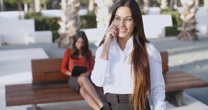 Attractive young woman chatting on a mobile. Attractive young woman standing in an urban square chatting on a mobile phone with a beaming smile of pleasure stock video footage
