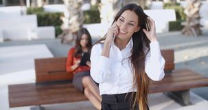 Attractive young woman chatting on a mobile. Attractive young woman standing in an urban square chatting on a mobile phone with a beaming smile of pleasure stock video