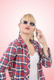 Attractive young woman in checkered shirt with a cell phone Royalty Free Stock Image