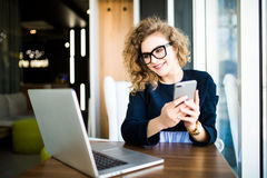 Attractive young woman checking her text messages on her mobile phone with a smile as she sits at her desk in the office. Look at. Woman checking her text Stock Photos