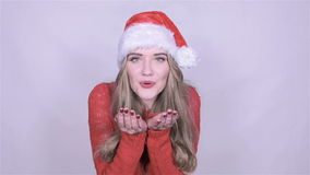 Attractive young woman in christmas hat sending a kiss on white background. stock video
