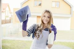 Attractive young woman cleaning windows in the house Royalty Free Stock Image