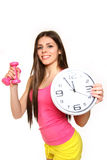 Attractive young woman with a clock and dumbbells on a white bac Stock Photo