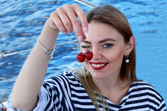 Attractive young woman coquettish eats cherry. dressed in a sailor suit. Sunny day. Stock Photography