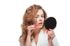 Attractive young woman correcting eyelashes and holding mirror. Isolated on white Stock Image