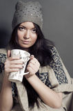 Attractive young woman in cozy clothes sitting Royalty Free Stock Photography