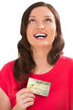 Attractive young woman with credit card looking up Royalty Free Stock Images