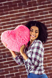 Attractive young woman cuddling with heart-shaped pillow Royalty Free Stock Image