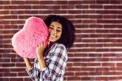 Attractive young woman cuddling with heart-shaped pillow Stock Images