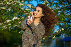 An attractive young woman with curly hair listening to music on your phone and smiling. On a background of beautiful flowering trees in the spring in the park Stock Photos