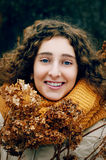 Attractive young woman with curly hair near dried hydrangea flow Royalty Free Stock Image