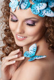 Attractive young woman with curly hairstyle and blue butterflies Royalty Free Stock Photos