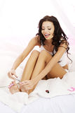Attractive young woman cutting her feat nails. In bed Royalty Free Stock Images