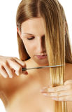 Attractive young woman is cutting her long natural hair. Stock Image