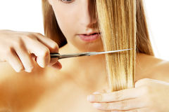 Attractive young woman is cutting her long natural hair. Stock Photography